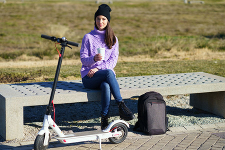 Female student with electric scooter taking a coffee break sitting on a bench outside her college