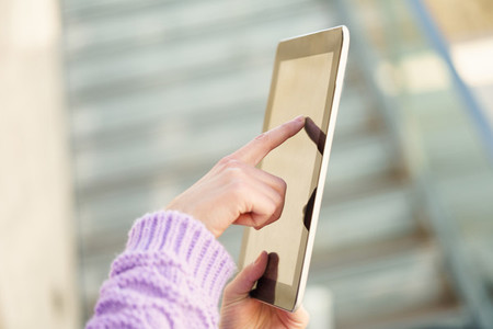 Detail of unrecognizable woman using digital tablet outdoors