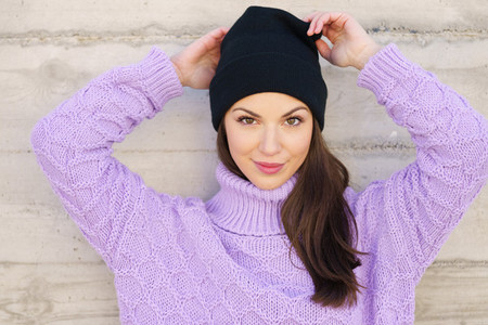 Happy young woman wearing winter hat against urban wall