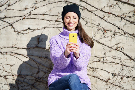 Happy young woman smiling sitting on a bench outdoors using a smartphone
