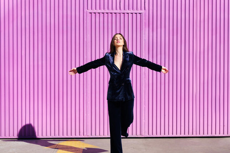 Woman wearing blue suit posing near pink shutter with open arms