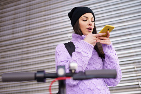 Woman in her twenties with electric scooter recording voice note with a smartphone outdoors