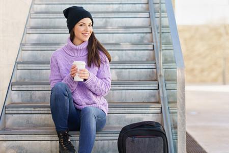 Woman in her twenties taking a coffee break sitting on some steps in the street