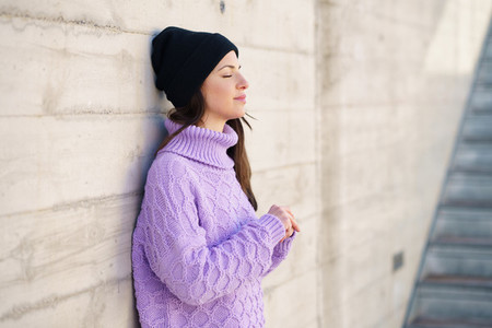 Woman in her twenties leaning against a wall outside with her eyes closed