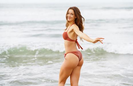 Woman with beautiful body enjoying her bath on the beach