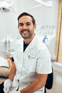 Happy young dentist in his clinic