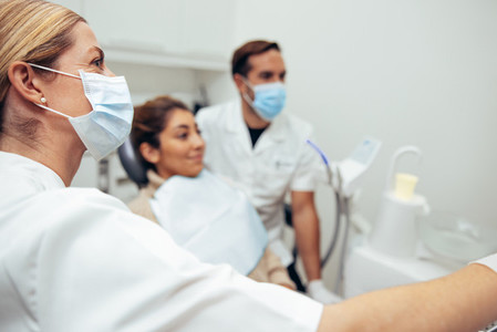 Female dentist with face mask showing x ray to patient