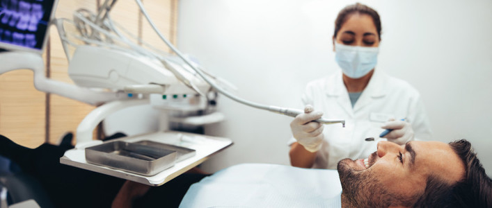 Male patient getting dental checkup in clinic