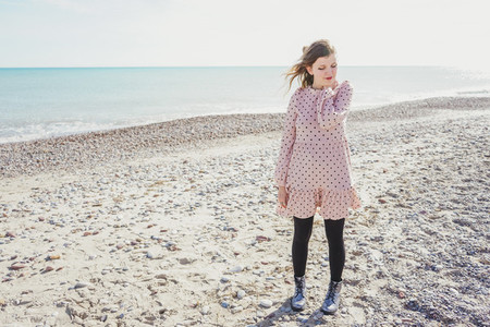 Young woman wearing a pink dress at the beach