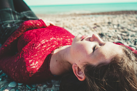Young and trendy woman in a sunny day sitting on the beach