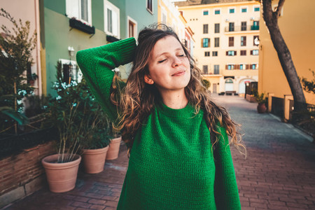 Young woman wearing green oversize sweater enjoying a windy day