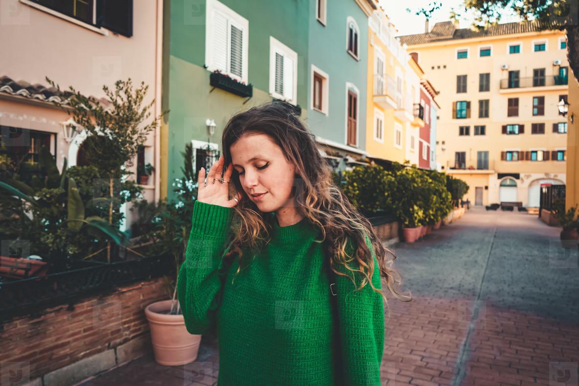 Young woman wearing green oversize sweater enjoying a windy day
