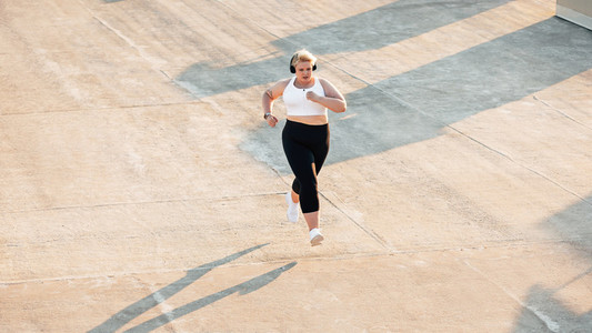 High angle view of plus size woman running outdoors Young curvy female