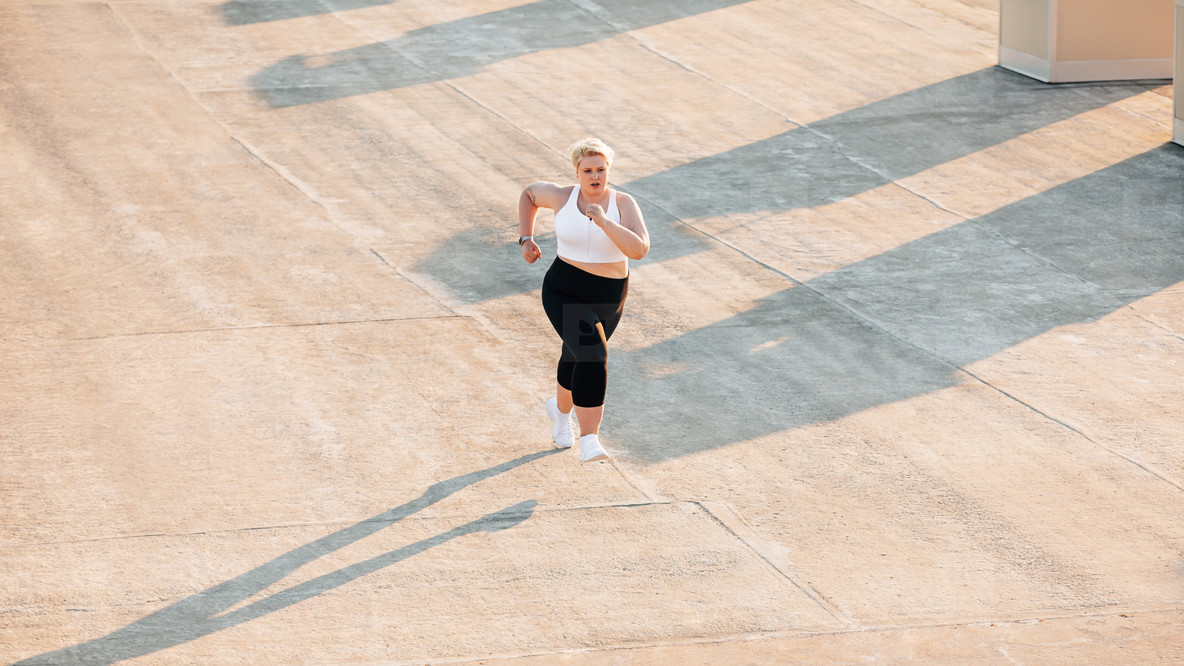 Plus size woman running on a roof  Young oversize female doing cardio training