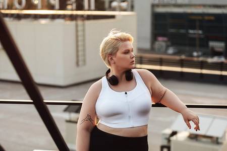 Woman with oversized body leaning to a railing during a workout on a roof Oversize fitness woman