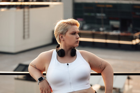 Side view of curvy woman with short hair leaning on a railing