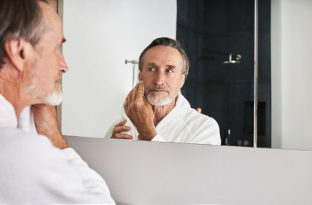 Senior man wiping his face with a towel in front of a mirror