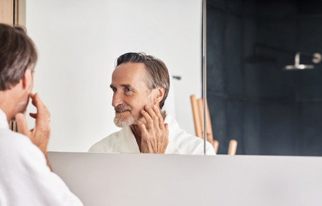 Smiling senior man looking at his reflection in the mirror and touching face  Mature male in a bathroom