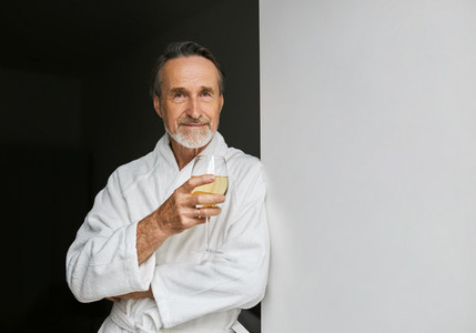 Portrait of a senior man leaning on a wall holding a glass
