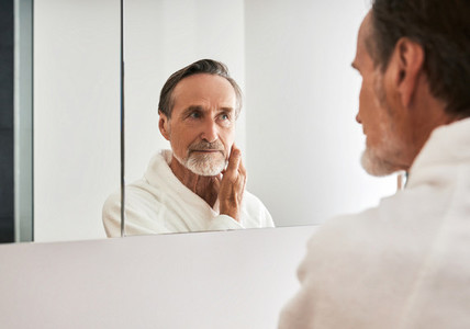 Mature man in a white bathrobe looking at a mirror in bathroom
