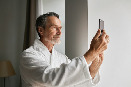 Senior man taking photographs on his smartphone
