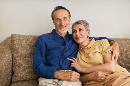 Portrait of smiling senior couple sitting on a couch in a living room  Two positive mature people embracing