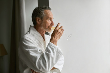 Side view of an elderly man drinking wine while looking at window in living room