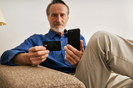 Close up of aged male hands holding a credit card and smartphone  Senior man using payment service at home