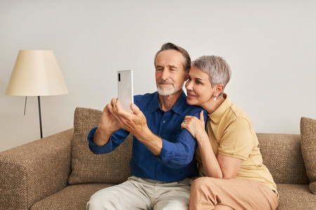 Senior couple spending time at home together  Elderly people taking a selfie while sitting on a couch