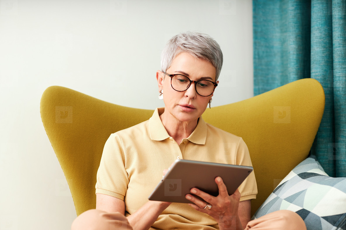 Mature woman sitting at home on armchair using digital tablet  Female in casuals watching content on a tablet