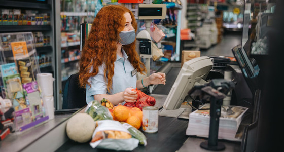 Female cashier working with protective mask