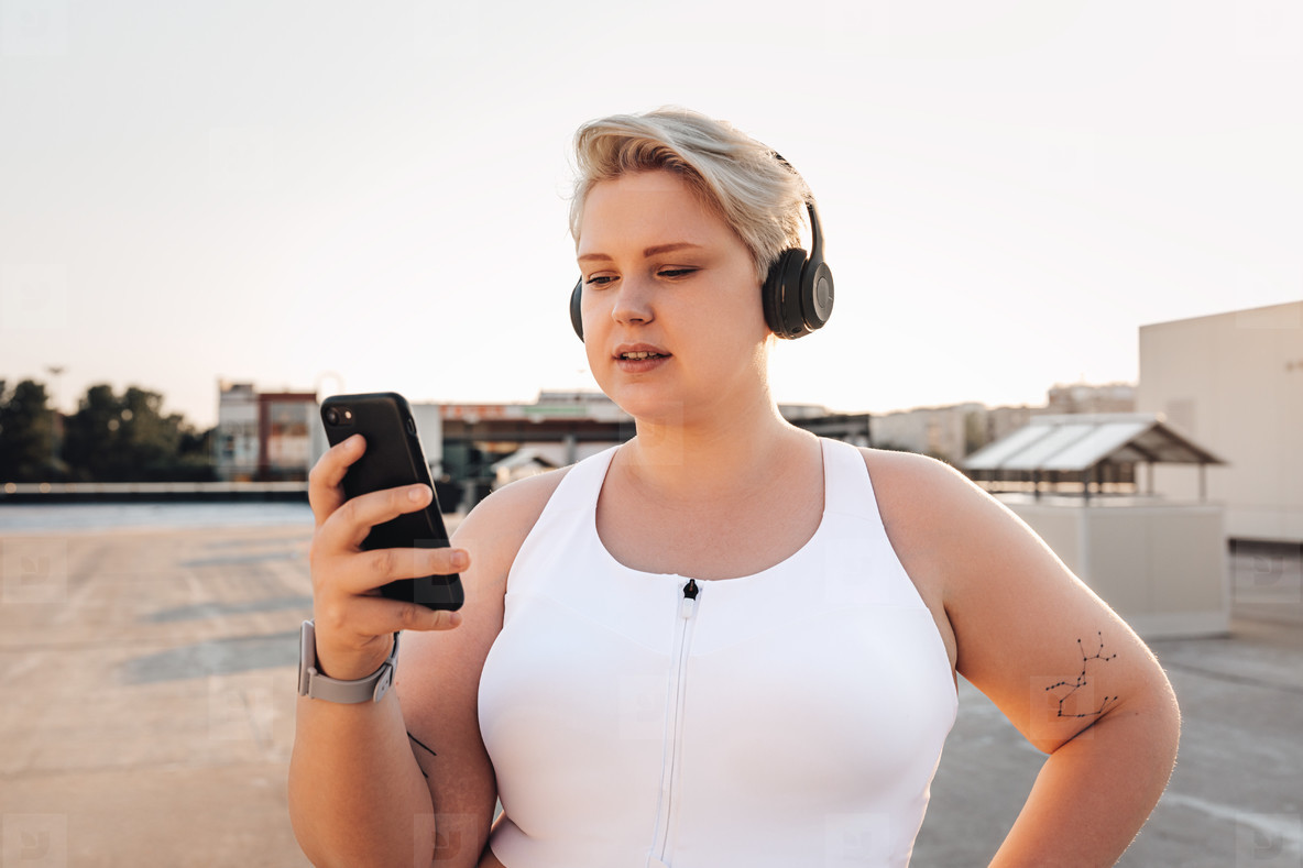 Oversize woman in sports clothes holding a smartphone while standing on the roof at sunset