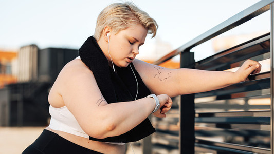 Side view of young plus size woman looking at a smartwatch  Sweated and exhausted curvy woman with a towel around her neck relaxing during training