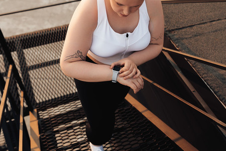 Unrecognizable curvy woman checking activity tracker while stepping up on staircase outdoors