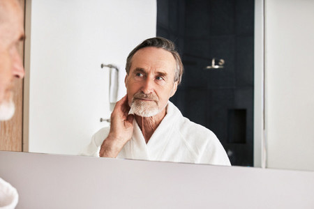 Bearded mature man inspecting his skin in front of a mirror