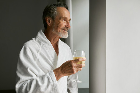 Smiling senior man with wineglass  Side view of a bearded mature male wearing a bathrobe in a hotel room looking at window