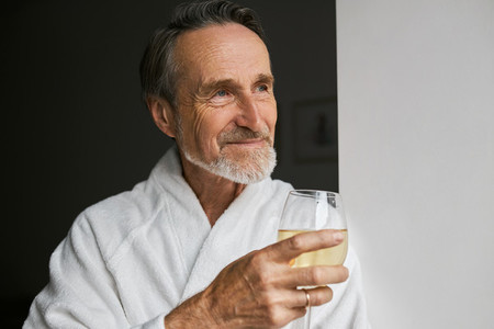 Close up of smiling mature man wearing white bathrobe holding wineglass looking away