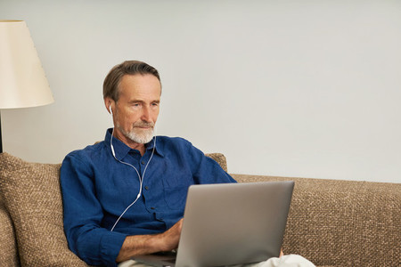 Senior man wearing earphones sitting on a couch with laptop