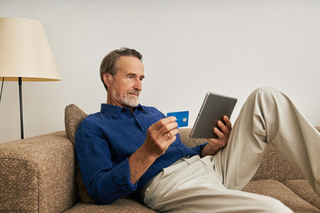 Handsome bearded man holding a digital tablet and credit card while sitting on a couch at home