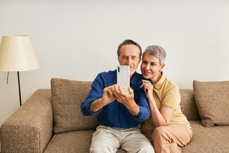 Senior couple in casuals at home sitting on couch taking a selfie