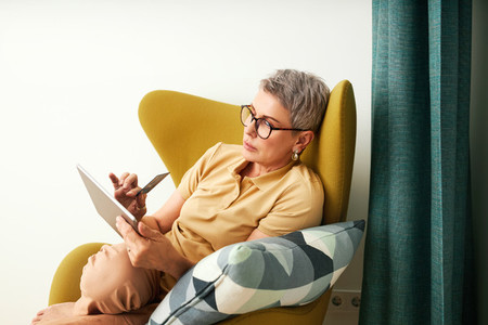 Stylish mature woman sitting in a yellow armchair in living room  Senior female shopping online