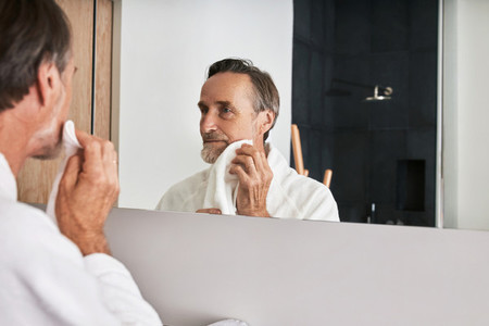 Handsome mature man wiping his cheek with a towel in a bathroom in front of a mirror