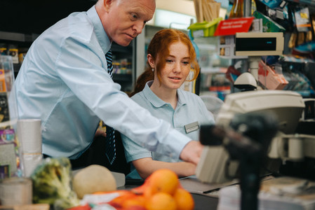 New cashier getting help from store manager at checkout