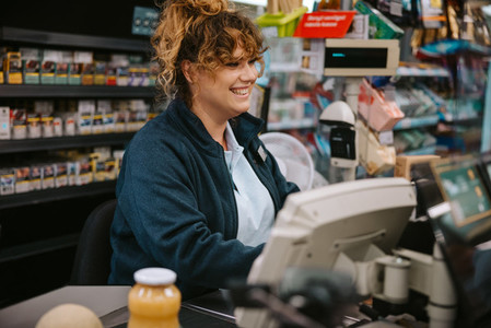 Female cashier working on cash register in a modern supermarket