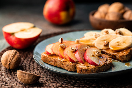 Toasts with peanut butter  apple  banana  walnut and honey  Healthy vegetarian breakfast concept