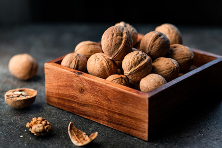 Close up of walnuts in a shell in a wooden box on a table