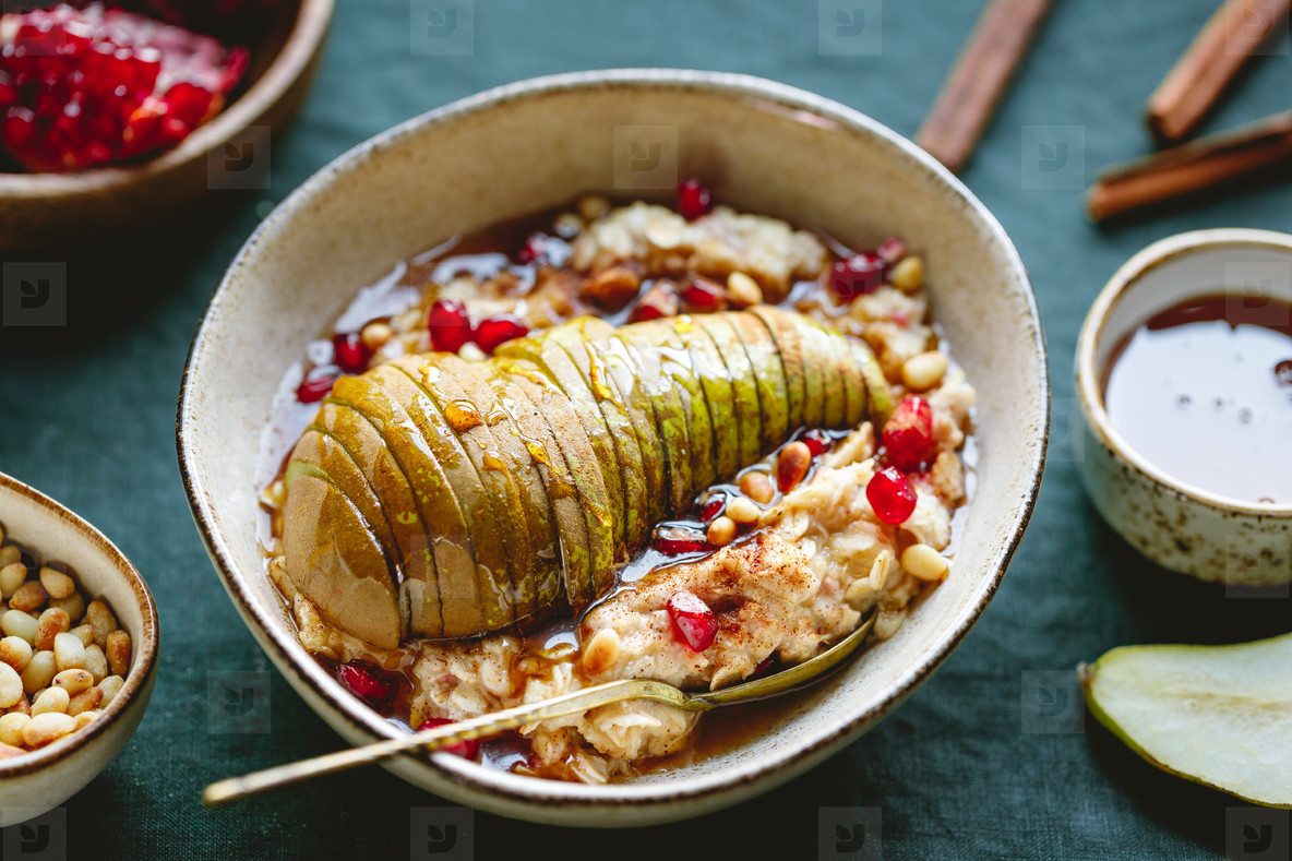Overnight oatmeal with cinnamon  honey  pear  pomegranate seeds and pine nuts  Healthy vegan breakfast