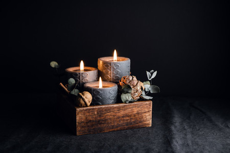 Decorations with wooden box and black burning candles in a dark interior