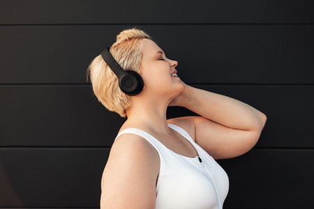 Plus size woman listening to music near a black wall Young curvy female taking a break during exercises