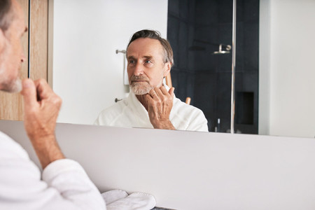 Handsome senior man wearing white bathrobe examine his skin in bathroom at morning